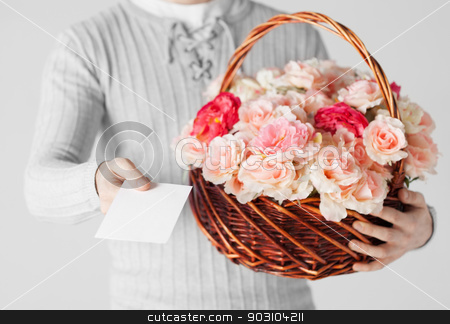 man holding basket full of flowers and postcard stock photo, close up of man holding basket full of flowers and postcard. by Syda Productions