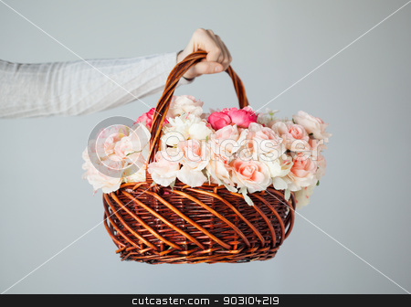 man's hand holding basket full of flowers stock photo, close up of man's hand holding basket full of flowers. by Syda Productions