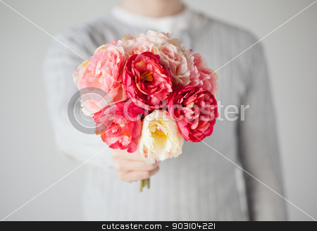 man giving bouquet of flowers stock photo, close up of young man giving bouquet of flowers. by Syda Productions