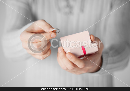 man holding wedding ring and gift box stock photo, close up of man holding wedding ring and gift box. by Syda Productions