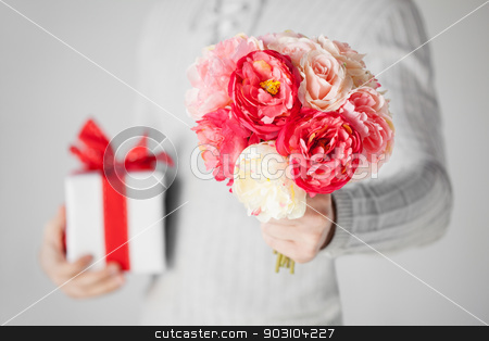 man holding bouquet of flowers and gift box stock photo, close up of man holding bouquet of flowers and gift box. by Syda Productions