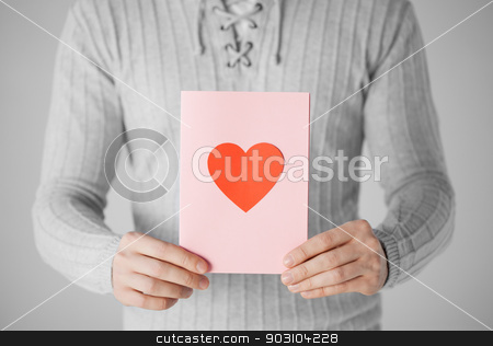 man holding postcard with heart shape stock photo, close up of man holding postcard with heart shape. by Syda Productions