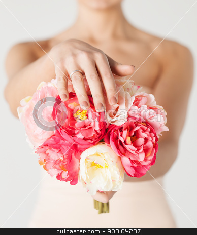 bride with bouquet of flowers and wedding ring stock photo, close up of bride with bouquet of flowers and wedding ring. by Syda Productions