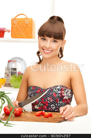 beautiful woman in the kitchen cutting vegetables stock photo, beautiful woman in the kitchen cutting vegetables.. by Syda Productions