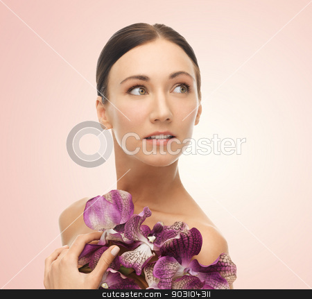 woman with orhid flowers stock photo, bright picture of relaxed woman with orchid flowers by Syda Productions