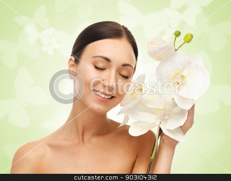 smiling woman with white orchid flower stock photo, bright picture of smiling woman with white orchid flower by Syda Productions
