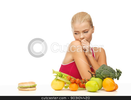 doubting woman with fruits and hamburger stock photo, picture of doubting woman with fruits and hamburger by Syda Productions