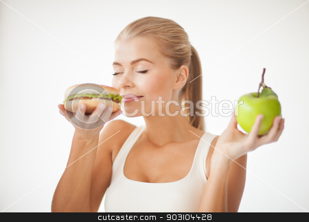woman smelling hamburger and holding apple stock photo, healthy woman smelling hamburger and holding apple by Syda Productions