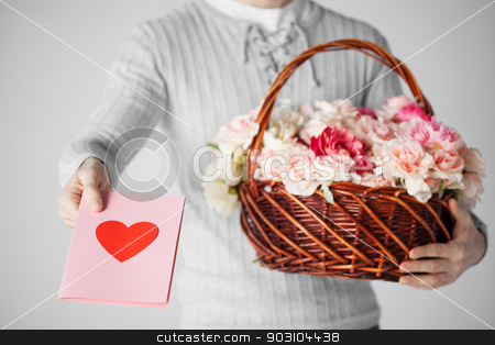 man holding basket full of flowers and postcard stock photo, man with basket full of flowers and giving postcard. by Syda Productions