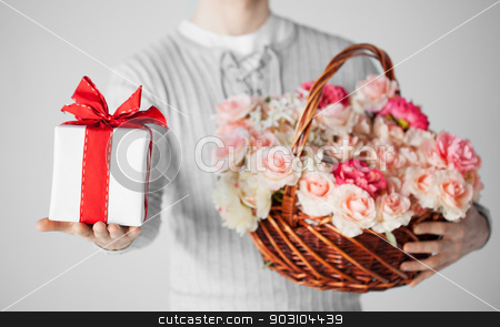 man holding basket full of flowers and gift box stock photo, close up of man holding basket full of flowers and gift box. by Syda Productions