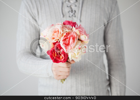 man holding bouquet of flowers stock photo, close up of young man holding bouquet of flowers. by Syda Productions