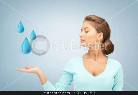 woman showing blue water drops stock photo, woman showing blue water drops on her hand by Syda Productions