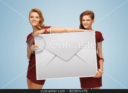 girls holding big envelope stock photo, picture of two lovely girls holding big envelope by Syda Productions