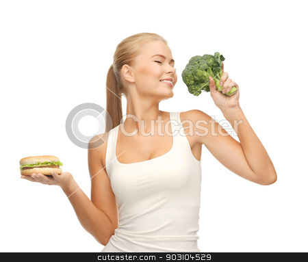 woman with broccoli and hamburger stock photo, picture of sporty woman with broccoli and hamburger by Syda Productions