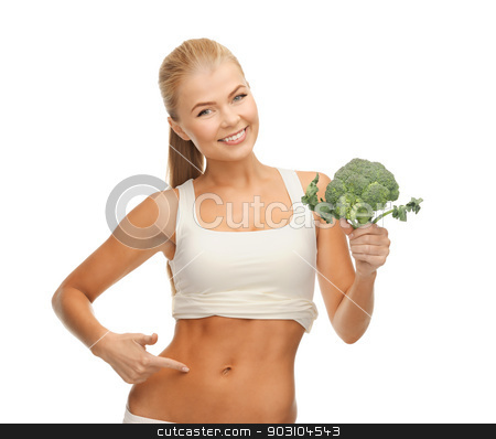 woman pointing at her abs and holding broccoli stock photo, beautiful woman pointing at her abs and holding broccoli by Syda Productions