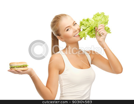 woman with green lettuce and hamburger stock photo, picture of sporty woman with green lettuce and hamburger by Syda Productions