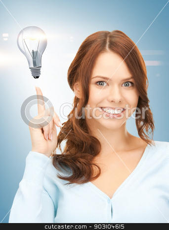 woman pointing her finger at light bulb stock photo, beautiful woman pointing her finger at light bulb by Syda Productions