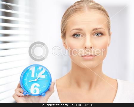 woman holding alarm clock stock photo, bright picture of woman holding alarm clock by Syda Productions
