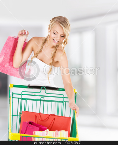 shopper stock photo, happy woman with shopping bags and cart by Syda Productions