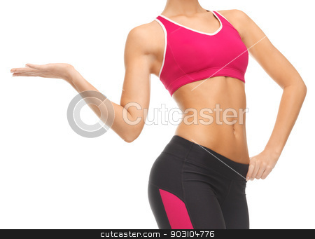 woman trained abs stock photo, close up of woman with trained abs showing something by Syda Productions
