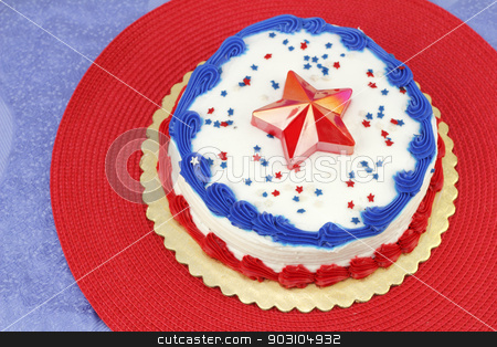 July 4th Decorated Cake stock photo, Round Independence Day holiday cake decorated with white frosting, red and blue ribbons, edible stars and a red plastic star on the center top. The cake is on a gold base, then red and blue placemats.  by Lee Serenethos