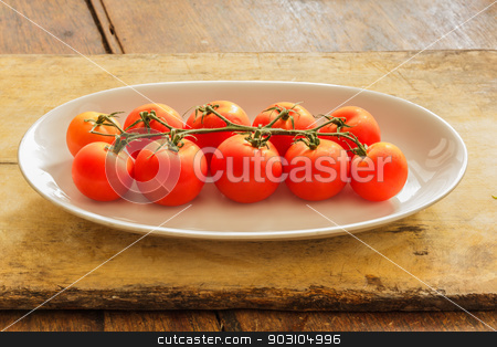 Cherry tomatoes in a dish on a table made of wood. stock photo, Cherry tomatoes on plate on wooden table in the kitchen. by SONGSAK  AROMYIM