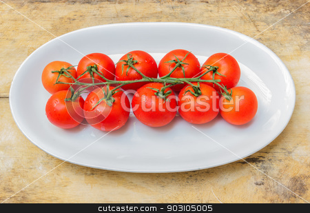 Cherry tomatoes in a dish on a table made ​​of wood. stock photo, Cherry tomatoes on plate on wooden table in the kitchen. by SONGSAK  AROMYIM