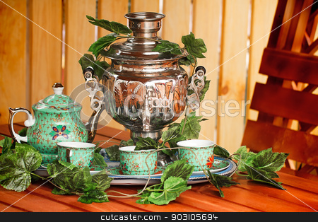 National Russian tradition to drink tea from a samovar. stock photo, Beautiful large samovar, cups and a kettle are standing on a table in expectation of the guests.  by Georgina198