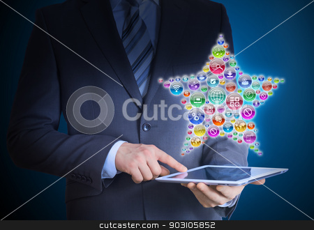 Businessman holding tablet in his hands stock photo, Businessman in a suit holding a tablet in his hands. Above the screen tablet application icons in the form of star by cherezoff