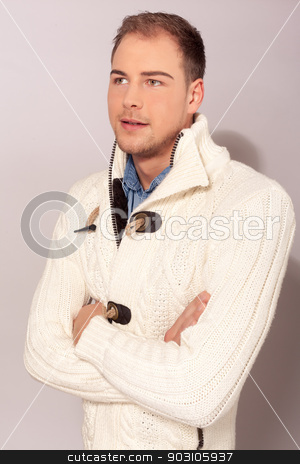 Stylish handsome young man stock photo, Stylish handsome unshaven young man in a cream winter sweater standing with folded arms looking at the camera with a smile by Roland Stollner