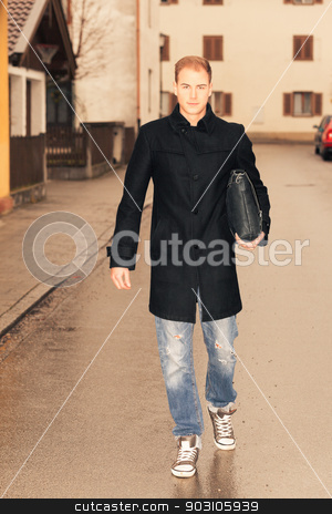 Confident stylish young man walking in town stock photo, Confident stylish handsome young man carrying a brief case under his arm walking through a deserted street in town by Roland Stollner