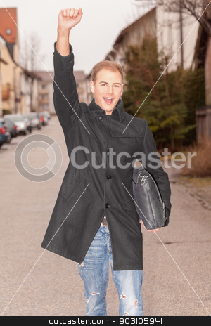 Handsome successful urban man cheering stock photo, Handsome stylish successful urban man cheering as he walks down a street in town with a brief case under his arm and his arm raised in jubilation by Roland Stollner