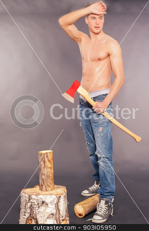 Muscular young man chopping logs stock photo, Muscular handsome young man in paint spattered jeans, sneakers and a bare chest standing chopping logs with an axe on a grey studio background by Roland Stollner