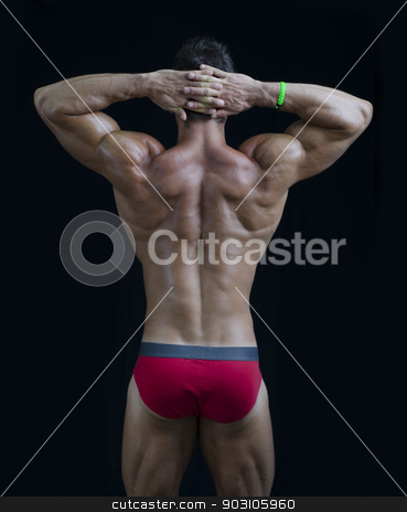 Young muscular bodybuilder's back, hands behind his head stock photo, Young muscular bodybuilder's back, hands behind his head. On black background by Stefano Cavoretto