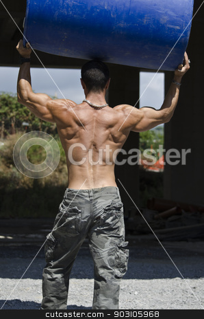 Back of muscular construction worker shirtless in building site holding big barrel stock photo, Muscular construction worker shirtless in building site holding big blue barrel over his head, shot from the back by Stefano Cavoretto