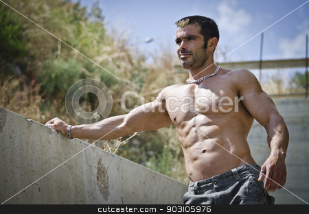Muscle man shirtless outdoors leaning against concrete wall stock photo, Muscle man shirtless outdoors leaning against concrete wall. Ripped abs, pecs and muscular arms by Stefano Cavoretto