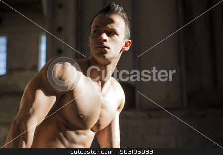 Muscular shirtless young man in abandoned warehouse standing stock photo, Muscular shirtless young man in abandoned warehouse standing, looking away. Copy-space by Stefano Cavoretto