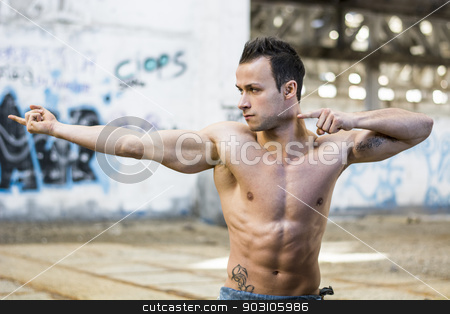 Muscular young man in abandoned warehouse pointing with fingers to a side stock photo, Muscular shirtless young man in abandoned warehouse standing, pointing with fingers to a side by Stefano Cavoretto