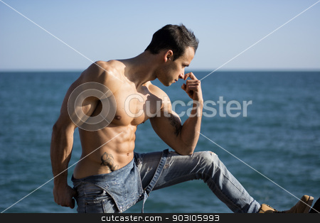 Muscular shirtless young man standing by the sea or ocean stock photo, Muscular shirtless young man standing by the sea or ocean, profile view by Stefano Cavoretto