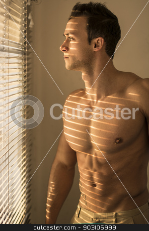 Muscular shirtless man lit by sun behind venetian blinds stock photo, Muscular shirtless man lit by sun behind venetian blinds, looking out of the window, sad by Stefano Cavoretto