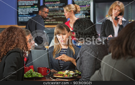Skeptical Business Woman with Group stock photo, Skeptical woman with coworkers meeting during lunch by Scott Griessel