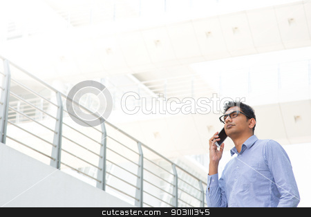 Indian businessman on the phone stock photo, Young Asian Indian businessman on the phone, male business man, real modern office building as background. by szefei