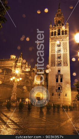 Giralda Bell Tower Seville Cathedral Rainy Night Spain stock photo, Giralda Spire, Bell Tower, Seville Cathedral, Rainy Night, Seville, Andalusia Spain.  Built in the 1500s.  Largest Gothic Cathedral in the World and Third Largest Church in the World.  Burial Place of Christopher Columbus.  Giralda is a former minaret converted into a bell tower by William Perry