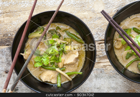 Bowls of Thai green curry with chopsticks stock photo, Bowls of tasty Thai green curry served with chopsticks made from nutritional bean sprouts, broccoli, chicken, coconut milk, coriander,and green beans, view from above by Stephen Gibson