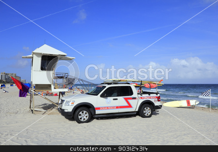 Ocean Rescue Truck stock photo, POMPANO BEACH, FLORIDA - DECEMBER 22, 2013: Pompano Beach Ocean Rescue truck next to a lifeguard tower with rescue surfboards, safety warning flags, with people and the Atlantic ocean on a sunny day.  by Lee Serenethos