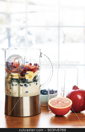 Preparing smoothies with fruit and yogurt stock photo, Healthy smoothie ingredients in blender with fresh fruit ready to blend on kitchen table by Elena Elisseeva