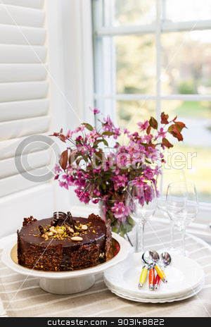 Chocolate cake stock photo, Round gourmet chocolate cake on table next to window with plates, cutlery, and pink spring bouquet by Elena Elisseeva