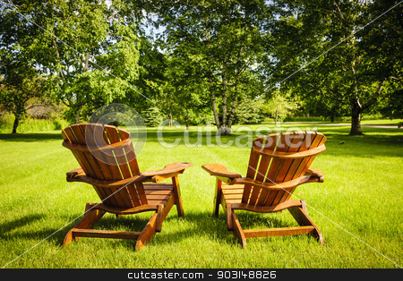 Summer relaxing stock photo, Two wooden adirondack chairs on lush green lawn with trees by Elena Elisseeva