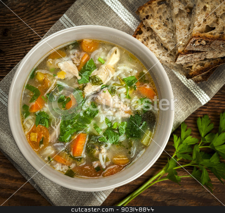Chicken soup with rice and vegetables stock photo, Chicken rice soup with vegetables in bowl and bread from above closeup by Elena Elisseeva
