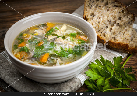 Chicken soup with rice and vegetables stock photo, Chicken rice soup with vegetables in bowl and bread on rustic table by Elena Elisseeva